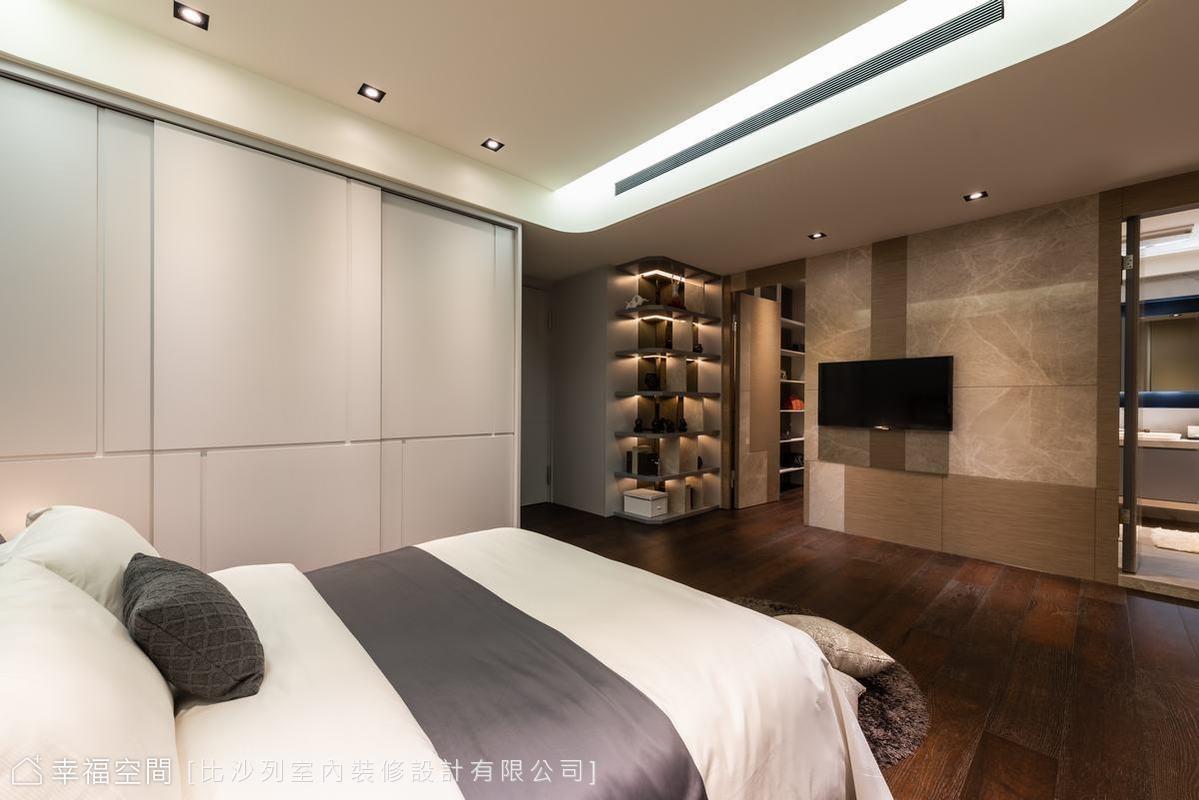 在石材拼接的主臥電視牆的兩側,更衣間與衛浴分別在左右採可互通的環狀動線設計,讓衛浴的光線得以間接串連至更衣空間。