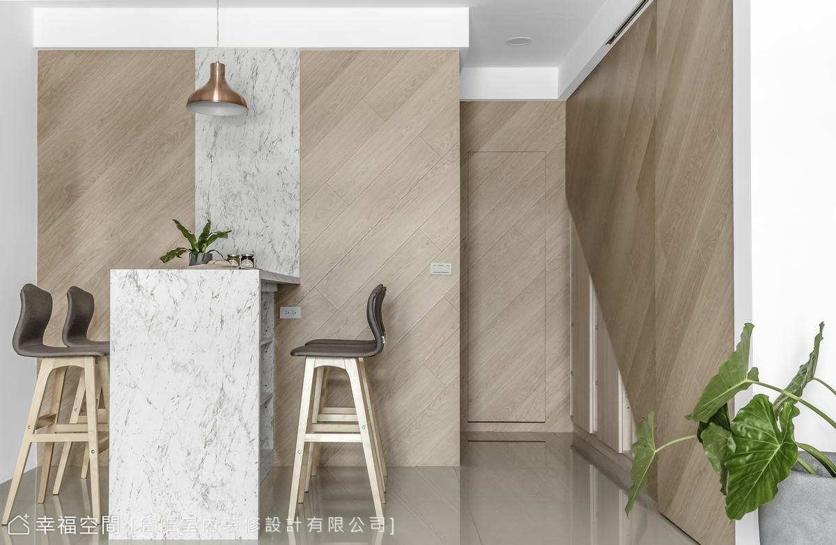 詹晧設計師跳脫傳統設計框架,將木地板移至餐廚區的牆壁立面,不僅巧妙區隔客餐廳空間,更營造溫馨的用餐氛圍。