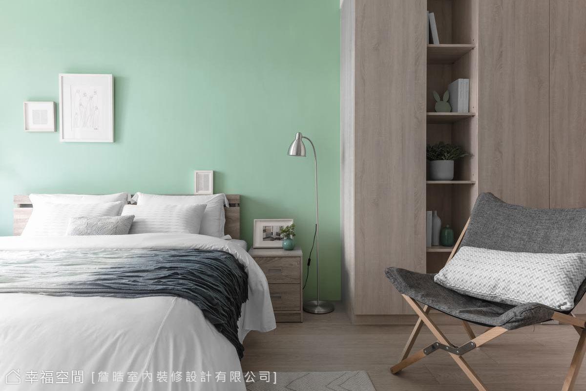 二樓的主臥空間以清新的嫩綠色與溫潤的木地板及櫃體鋪敘,型塑自然紓壓的眠寢空間。